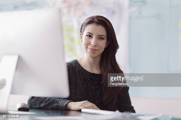 portrait of woman next to computer in studio office - real estate office stock photos and pictures