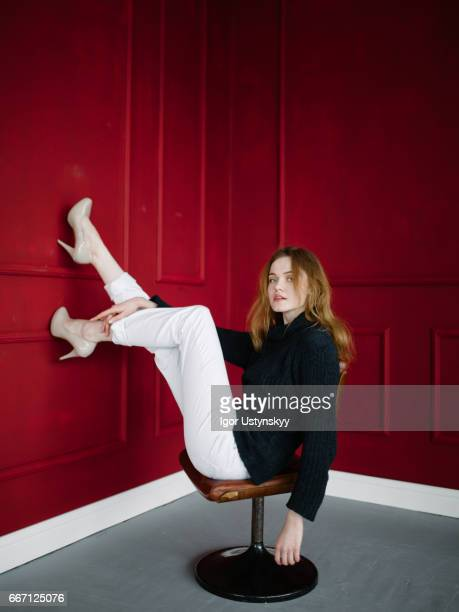 Portrait of woman on chair in red room