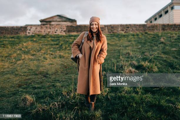 portrait of woman on grassy hill, calton hill, edinburgh, scotland - winter coat stock pictures, royalty-free photos & images