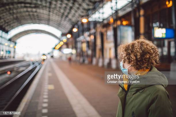 portrait of woman on railroad station wearing a mask - bortes stock pictures, royalty-free photos & images