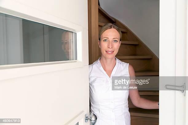 Portrait of woman opening door, Goirle, Brabant, Netherlands