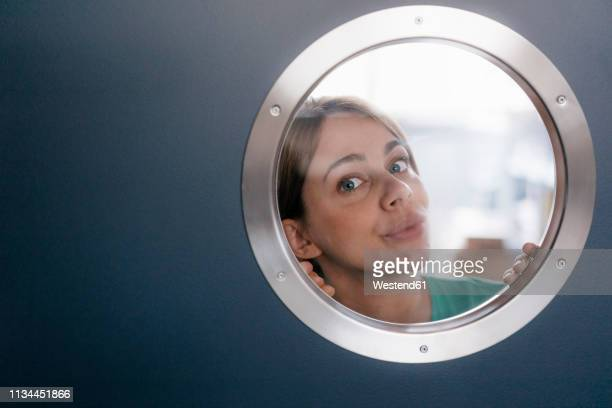 portrait of woman peeking from behind porthole - porthole stock photos and pictures