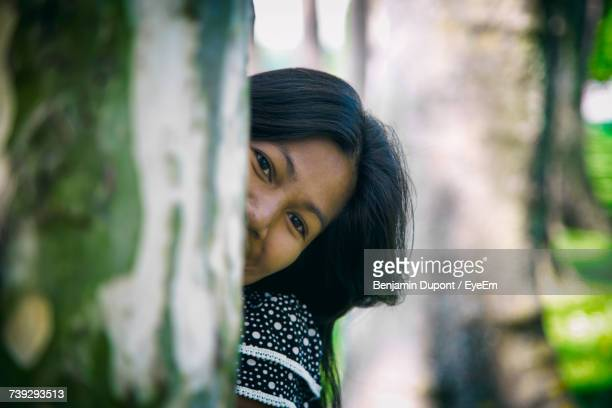 Portrait Of Woman Peeking From Behind Tree