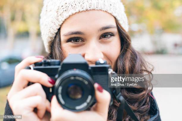 Portrait Of Woman Photographing Through Camera In City During Winter