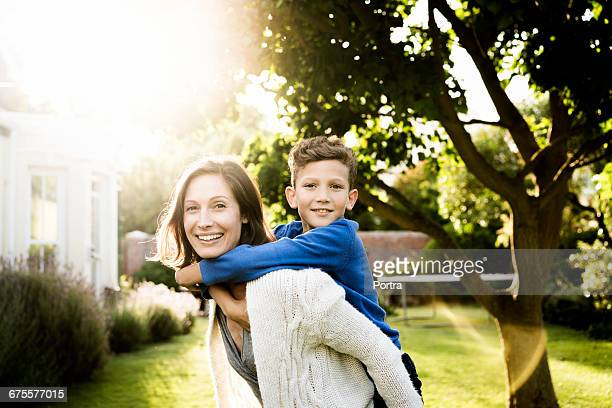 Portrait of woman piggybacking son in yard