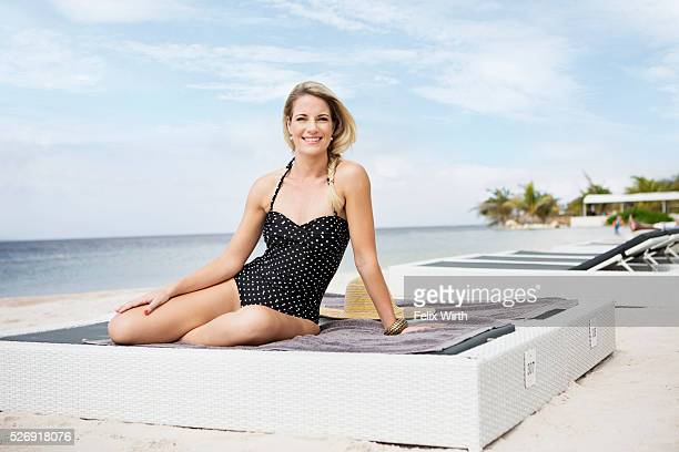 Portrait of woman posing on deck chair on beach