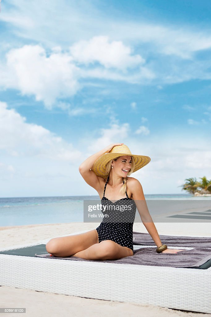 Portrait of woman posing on deck chair on beach : Stockfoto