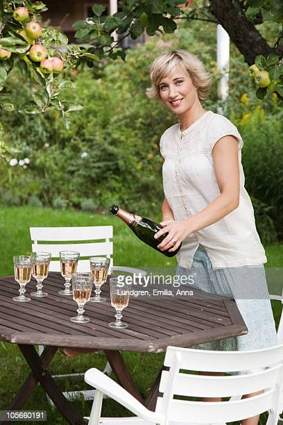 Portrait of woman pouring champagne at outdoor table