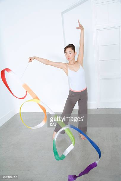 Portrait of woman practicing rhythmic gymnast performing with ribbon