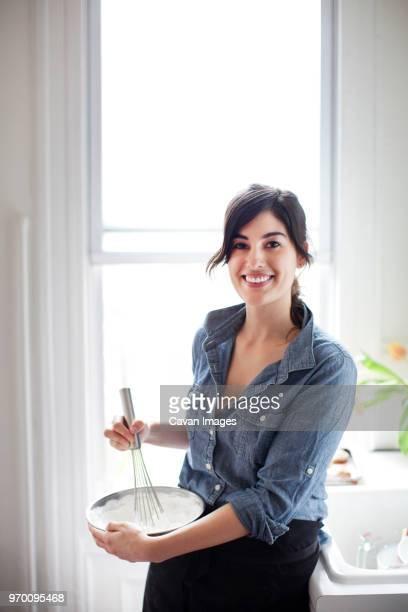 portrait of woman preparing whipped cream at home - azotes fotografías e imágenes de stock