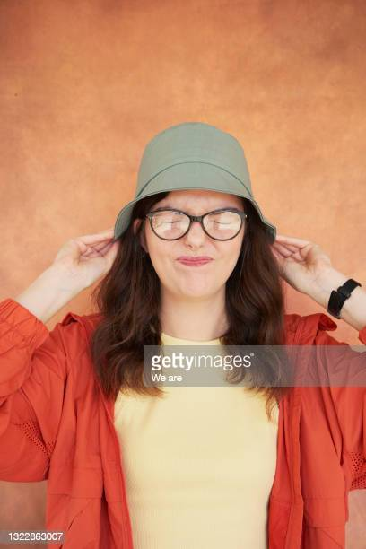 portrait of woman pulling down hat - headwear stock pictures, royalty-free photos & images