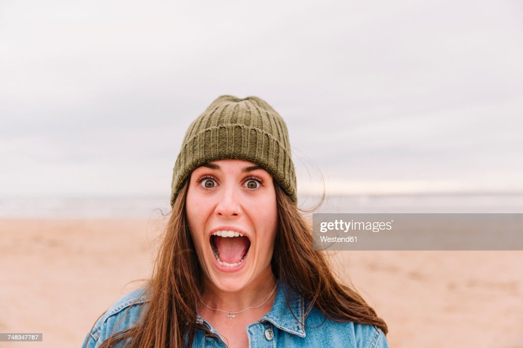Portrait of woman pulling funny face on the beach : Stock Photo