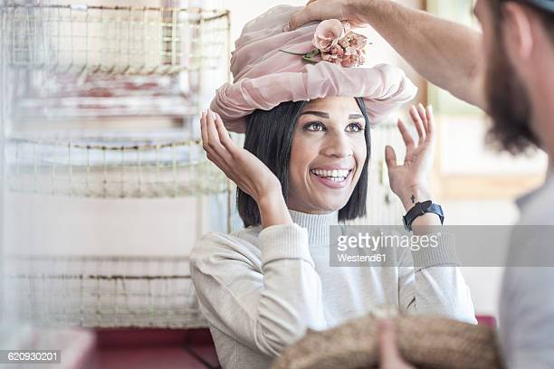 Portrait of woman putting on an old hat in antique shop