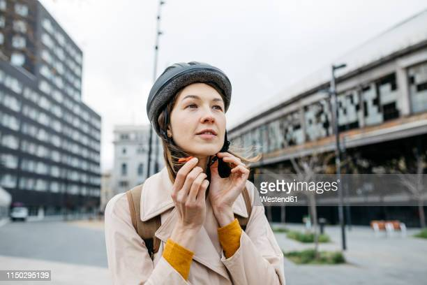 portrait of woman putting on bicycle helmet in the city - cycling helmet stock pictures, royalty-free photos & images