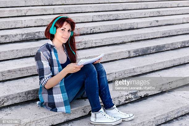 Portrait Of Woman Reading Papers While Listening To Music Through Headphones At Steps