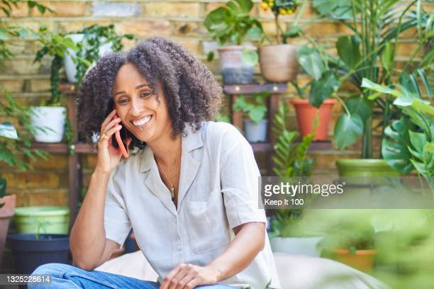 portrait of woman relaxing at home in her garden - one mid adult woman only stock pictures, royalty-free photos & images
