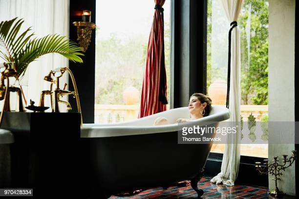 Portrait of woman relaxing in bathtub in boutique hotel
