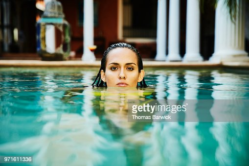 Portrait of woman relaxing in pool in courtyard of luxury hotel