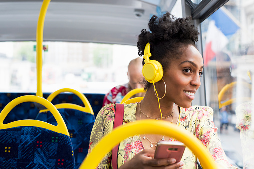 Portrait of woman relaxing on a bus wearing headphones - gettyimageskorea
