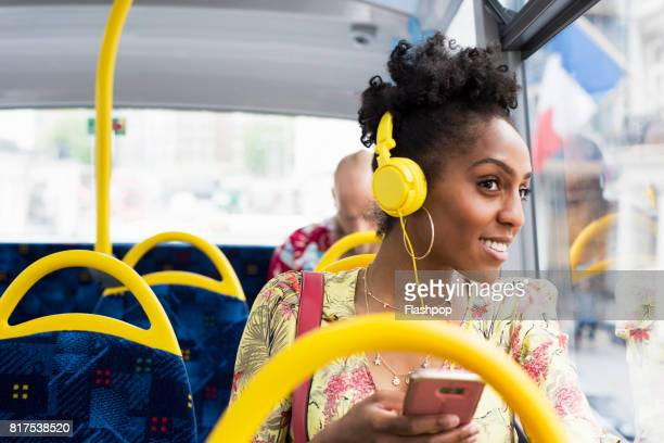 portrait of woman relaxing on a bus wearing headphones - transporte público imagens e fotografias de stock