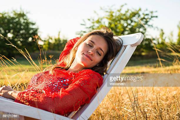 Portrait of woman relaxing on a deck chair on a meadow