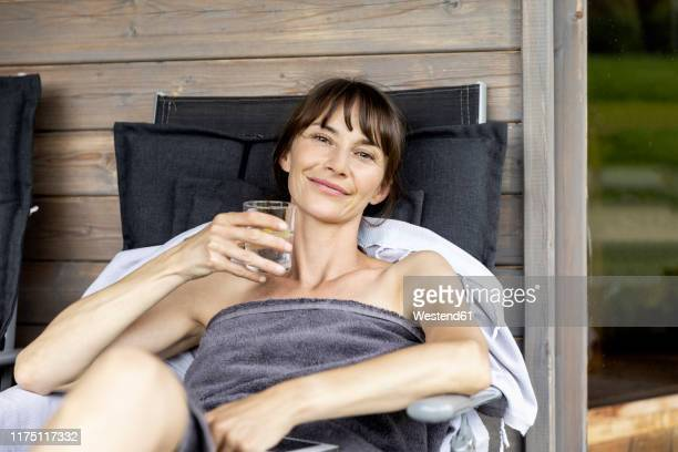 portrait of woman relaxing on a lounge holding glass of water - one mature woman only stock pictures, royalty-free photos & images