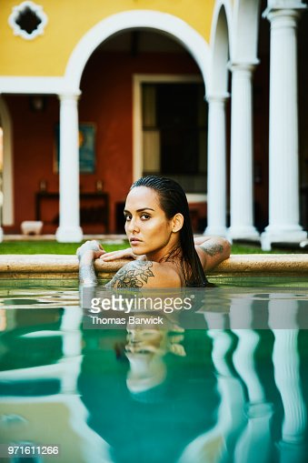 Portrait of woman relaxing on edge of pool in outdoor spa