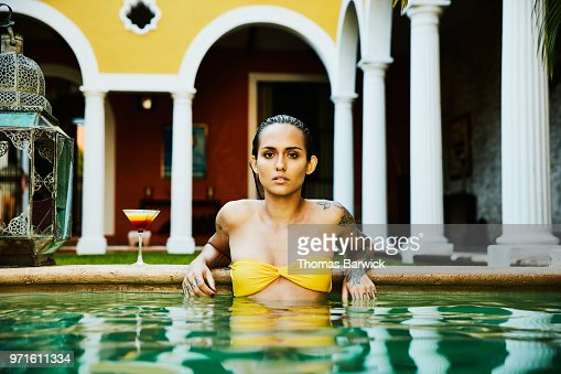 Portrait of woman relaxing on edge of pool with drink in courtyard of boutique hotel