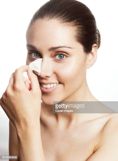 portrait of woman removing blackheads of nose against white background - blackheads stock photos and pictures