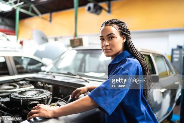portrait of woman repairing a car in auto repair shop - stereotypical stock pictures, royalty-free photos & images