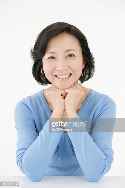 Portrait of woman resting chin on hands, studio shot