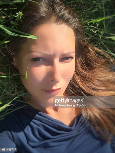 portrait of woman resting on grassy field - anfang stock pictures, royalty-free photos & images