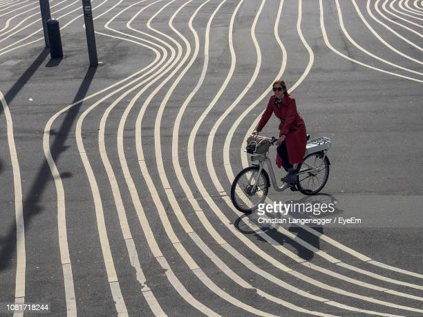 portrait of woman riding bicycle on road in city - copenhagen stock pictures, royalty-free photos & images