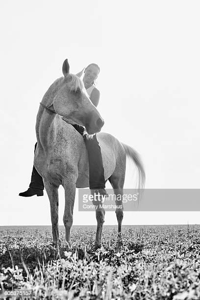 B&W portrait of woman riding horse bareback in field