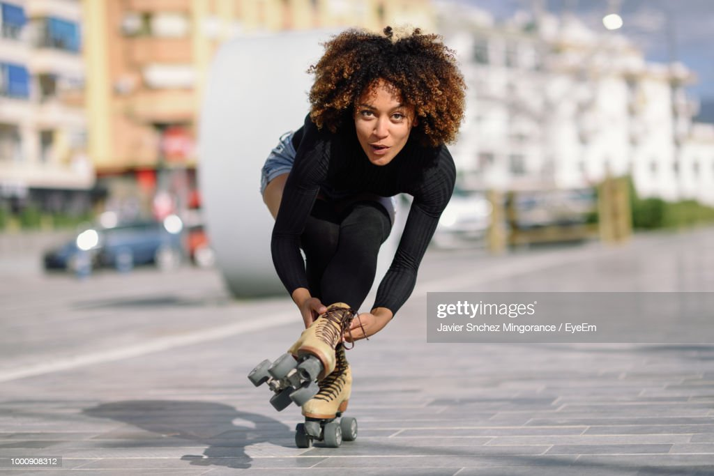 Portrait Of Woman Roller Skating On Sidewalk In City : Foto de stock