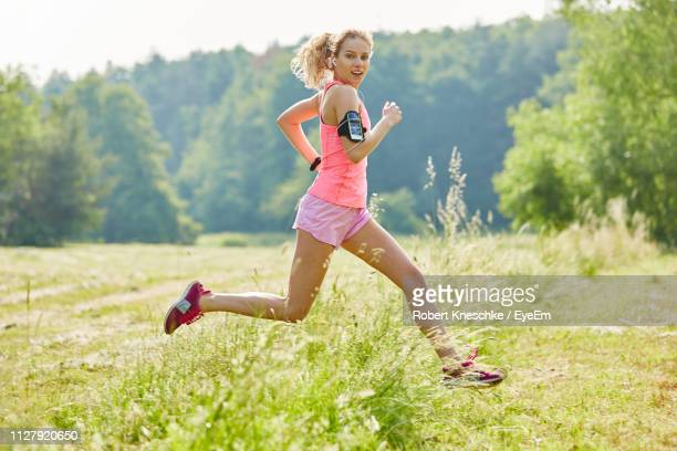 portrait of woman running on field - joggeuse photos et images de collection