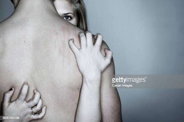 portrait of woman scratching mans back against gray background - human back stock photos and pictures