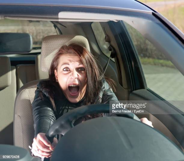 portrait of woman screaming in car - horrible car accidents stock pictures, royalty-free photos & images