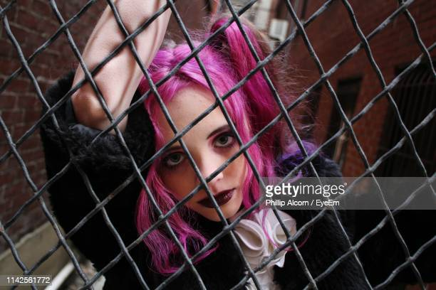 portrait of woman seen through chainlink fence - woman prison stock-fotos und bilder