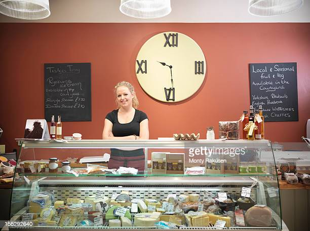 portrait of woman serving on farm shop delicatessen counter selling cheese and meat with large clock on wall - delicatessen stock photos and pictures