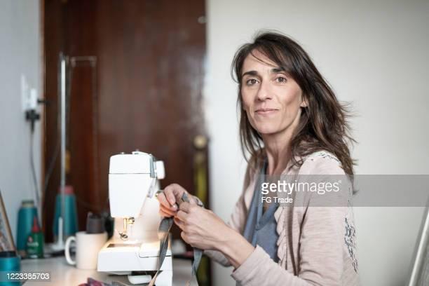 portrait of woman sewing at home - dedicação imagens e fotografias de stock