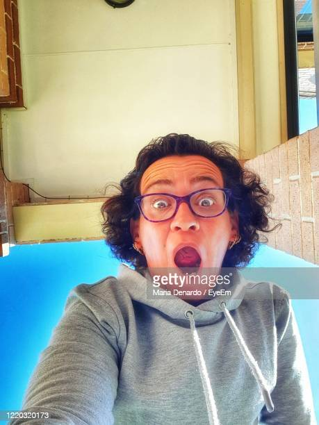 portrait of woman shouting at home - pulling funny faces stock pictures, royalty-free photos & images