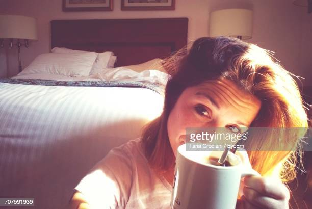 Portrait Of Woman Showing Coffee Cup At Home