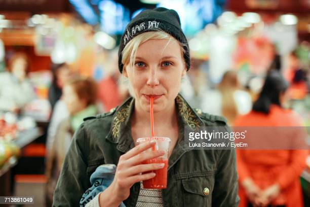 portrait of woman sipping drink - drinking straw stock pictures, royalty-free photos & images