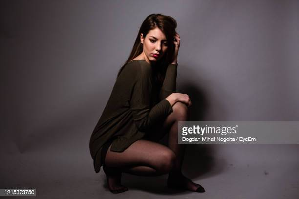 portrait of woman sitting against wall - bogdan negoita stock pictures, royalty-free photos & images