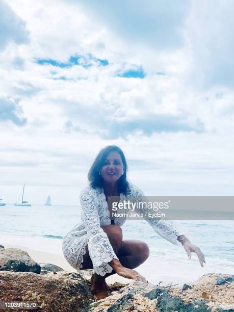 portrait of woman sitting at beach by sea against sky - naomi jarvis stock pictures, royalty-free photos & images