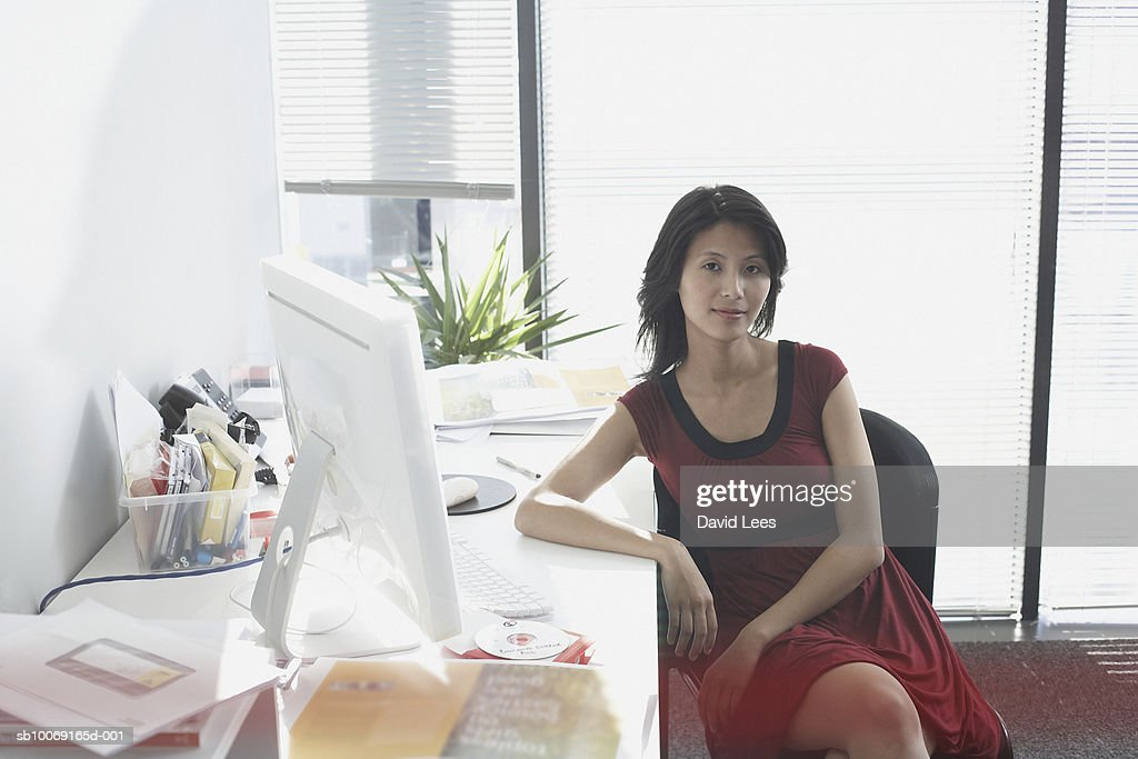 Portrait of woman sitting at desk in office : Stockfoto