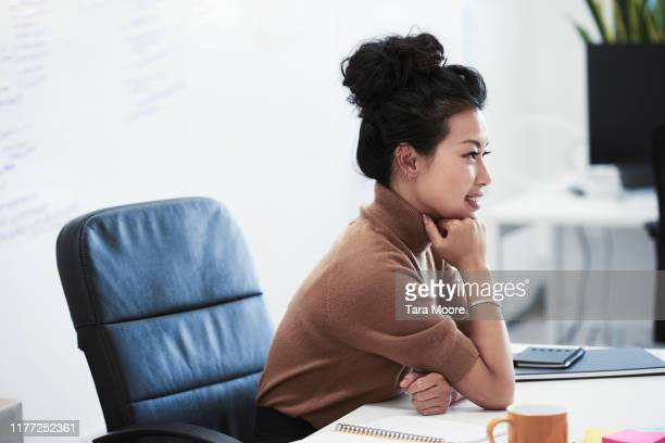portrait of woman sitting at desk - haar naar achteren stockfoto's en -beelden
