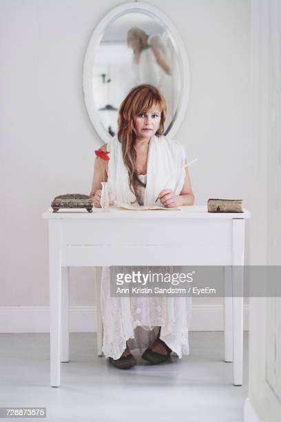 Portrait Of Woman Sitting At Desk With Angel Reflection In Mirror