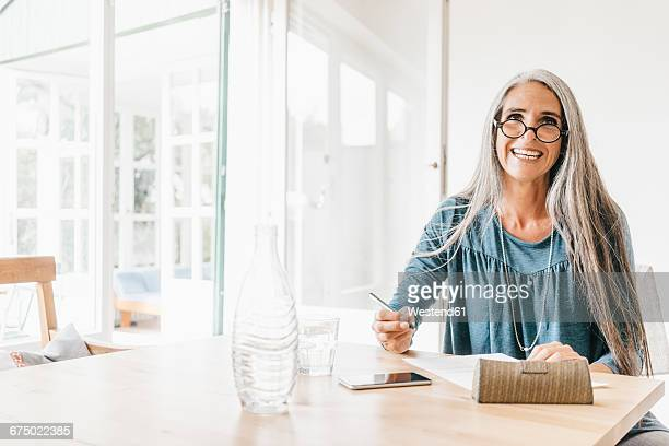 Portrait of woman sitting at table writing down something